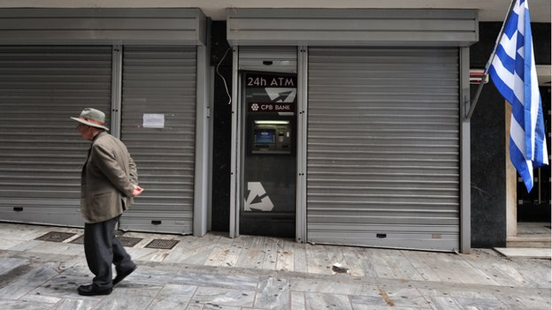 A man in Cyprus outside a closed bank