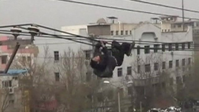 A drunk man climbing a utility pole and crawled along electricity cables in China