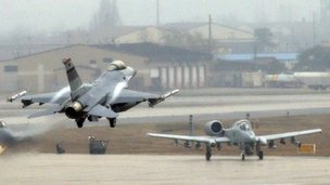 A F-16 fighter jet (C) comes in for a landing as A-10 jets move to take off at a U.S. air force base in Osan, south of Seoul