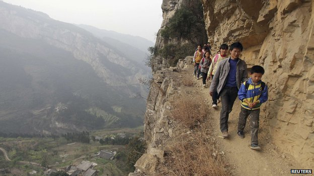 Students walking to school on narrow paths along the side of a mountain in China