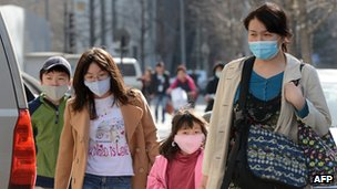 A Chinese family wearing face masks to protect against air pollution walk along a street in Beijing on March 27, 2013.