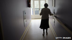 A dementia sufferer walks down a care home corridor.