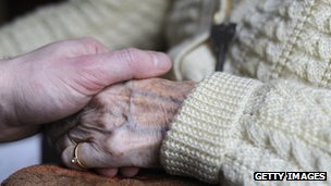 Relative holds the hand of an Alzheimer's sufferer