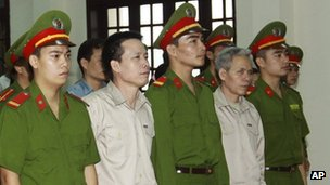 In this April 2, 2013 file photo, Doan Van Vuon, second from left and his brother Doan Van Sinh, fourth from left, stand trial at the court in the northern city of Haiphong, Vietnam.
