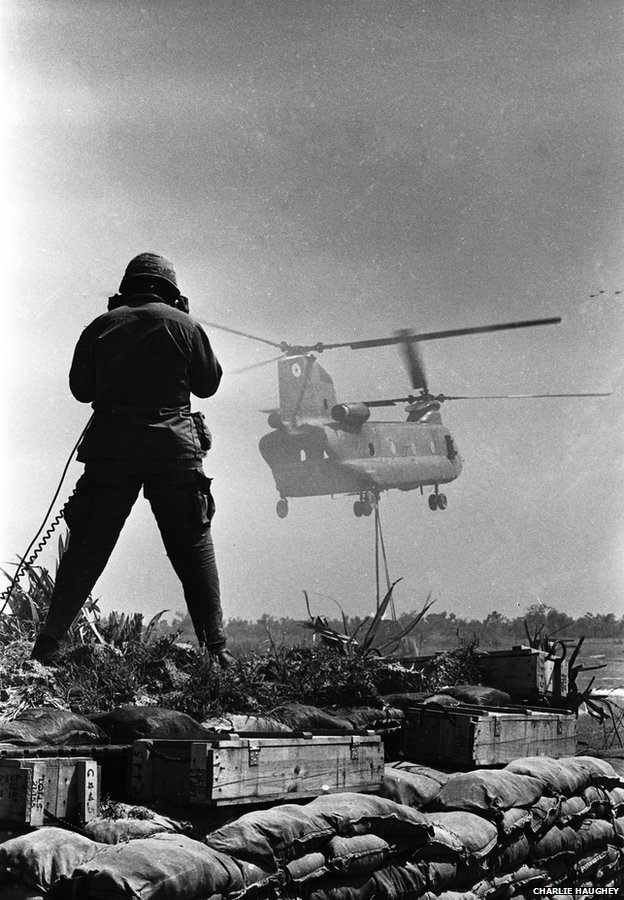 An RTO (radio telephone operator) guides a Chinook delivering a sling load of materials and supplies at Fire Support Base Pershing, near Dau Tieng
