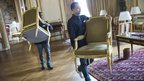 Workers carry pieces of furniture that are being auctioned at the Crillon Hotel, in Paris