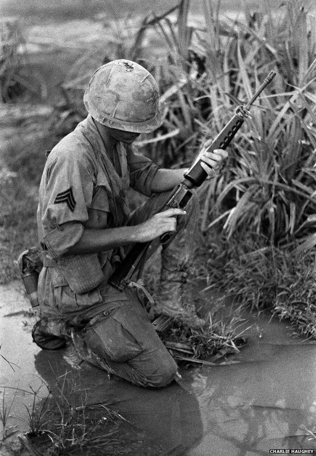 A Sergeant kneels on wet ground and checks his M16
