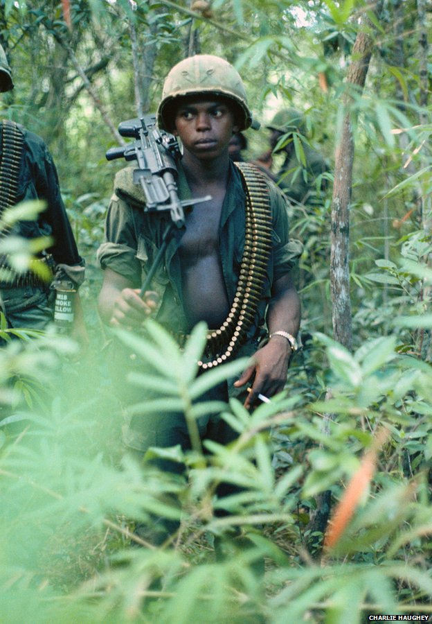 An alert, young M60 machine gun operator in the jungle