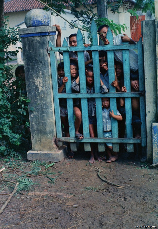 Vietnamese children peer through a gate at Haughey's camera