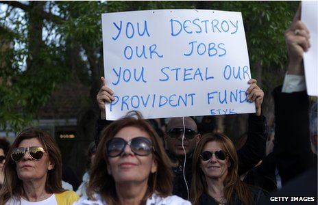 "A protestor holding a sign saying ""You destroy our jobs, you steal our provident funds"""