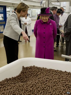 The Queen and Fiona Dawson (left), President of Mars Chocolate UK, look at a vat containing Maltesers