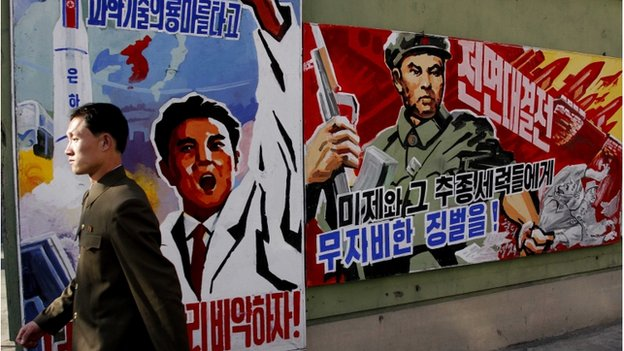 A North Korean man walks past propaganda posters in Pyongyang, March 26