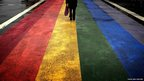 A pedestrian walks across a rainbow pedestrian crossing painted on Sydney's Oxford street,