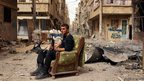 A member of the Free Syrian Army holds his weapon as he sits on a sofa in the middle of a street in Deir al-Zor