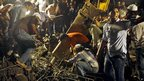 Rescue workers search the rubble at the scene of the collapsed building in Thane, Mumbai, on 4 April 2013