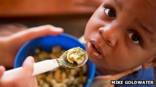 A boy from the orphanage eating his meal fortified with moringa leaves