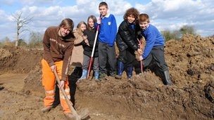Children and a workman digging on a patch of mud