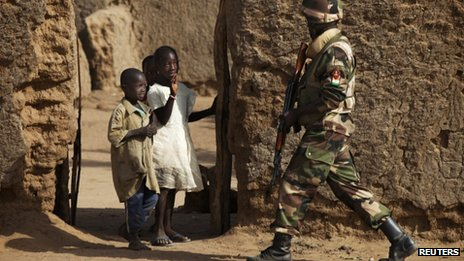 Children wave at a soldier from Niger on patrol in Gao, 27 February 2013