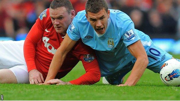 Wayne Rooney (left) challenges Edin Dzeko
