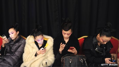 Four women look at mobile phones while sitting next to each other