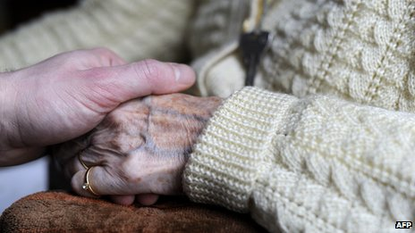 Close-up of somebody holding and elderly lady's hand