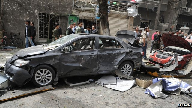 Photo released by the Syrian official news agency SANA, shows Syrians inspecting a damaged car at the scene of a car bomb attack near the Sabaa Bahrat Square