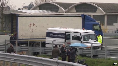 One of the vans targeted in the robbery in Italy and the lorry the robbers used to block the road