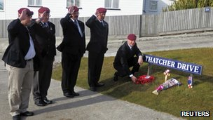 A group of former British paratroopers who fought in the Falklands War, salute as they leave a wreath for former British prime minister Margaret Thatcher at a street sign in her name after hearing of her death, in Port Stanley April 8