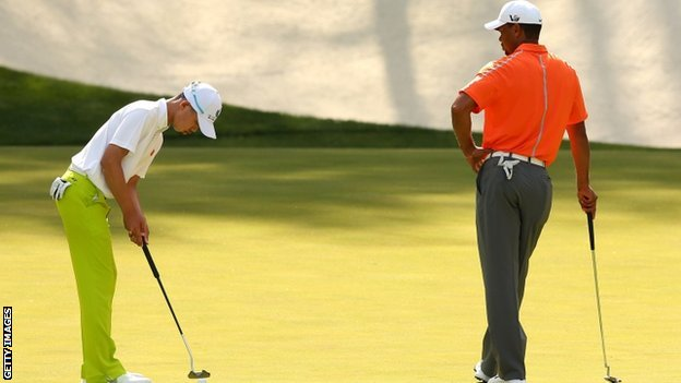 Tiger Woods watches as Guan Tianlang putts