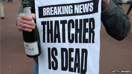 A man holds a bottle of champagne next to a newspaper poster carrying the news of Thatcher's death