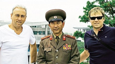 Nigel Green and his cousin Andrew Drury pose with a North Korean guard
