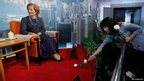 A staff member lays a flower in front of the wax statue of former British Prime Minister Margaret Thatcher