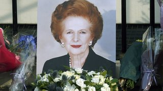 A portrait of Margaret Thatcher with a floral tribute