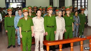 Fisher farmer Doan Van Vuon (second left, front row) and his family members stand trial at a local People's Court House in the northern coastal city of Haiphong, 2 April 2013