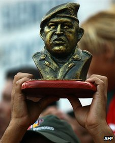 "Chavez supporter holds the bust of ""El Comandante"""