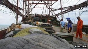 Members of the Philippine Coast Guard inspect the Chinese fishing vessel that ran aground on Monday in the Tubbataha Reef in Palawan province, 9 April 2013