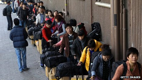 Visitors from mainland China wait in a queue with their goods outside the Sheung Shui train station in Hong Kong