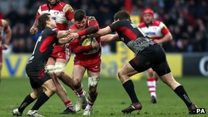 Gloucester Rugby's Freddie Burns is tackled by two London Welsh players