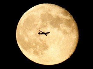 Jet flies in front of moon