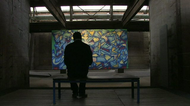 A man looks at an artwork in the factory