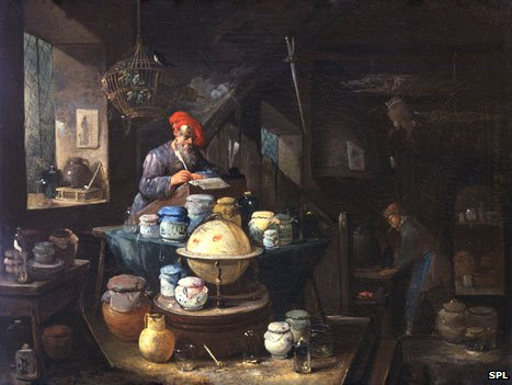 17th Century painting showing an alchemist and his servant in a cluttered study