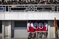 Members of the Korean Children's Union in red and white chat while spectators take their seats at a stadium