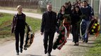 Mourners arrive at a cemetery prior to a mass funeral for the victims of a shooting in the village of Velika Ivanca,