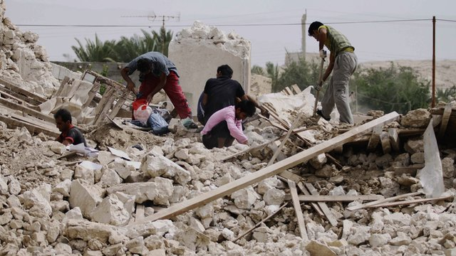 Iranians collect their belongings from the rubble of a destroyed house