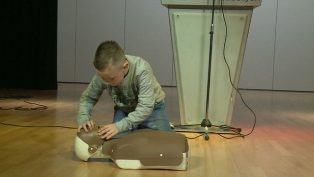 Schoolchild practising first aid on dummy