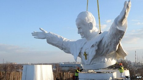 Workers put together elements of a 13.8m tall sculpture of the late Pope John Paul II in Czestochowa, southern Poland, 7 April 2013