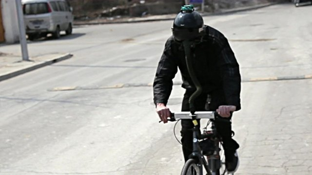 "Matt Hope wearing fighter pilot helmet while riding the ""breathing bike"""
