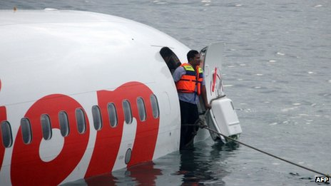 A man stands in the cabin door of the crashed plane near Denpasar airport, Bali, 13 April