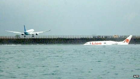 The crashed jet lies in water as another plane lands at Denpasar airport, Bali, 13 April