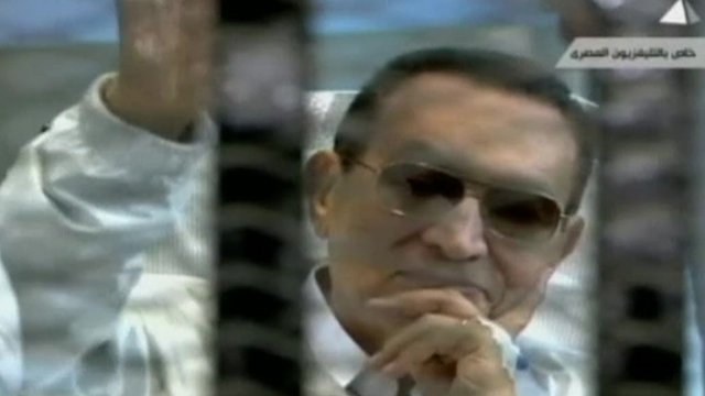 Hosni Mubarak in court, smiling and waving